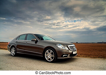 Front view of a luxury car on country road with dramatic sky