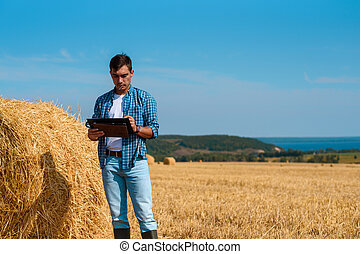 Front view of a male agronomist farmer with a tablet in blue jeans and a shirt and a white t-shirt in a field with haystacks