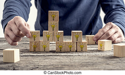 Front view of a man arranging wooden blocks with hand drawn...