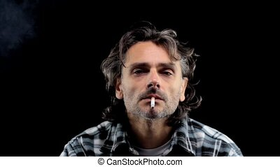 smoking - front view of a man smoking over black background