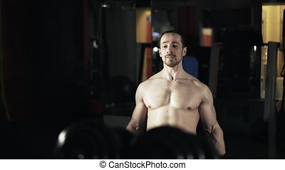 Front view of a man with naked torso doing a dumbbell exercise in gym