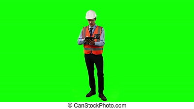 Front view of a Caucasian man wearing a helmet and high visibility vest, counting and using his tablet on green screen background.