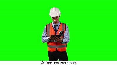 Front view of a Caucasian man wearing a helmet and high visibility vest, using his tablet on green screen background.