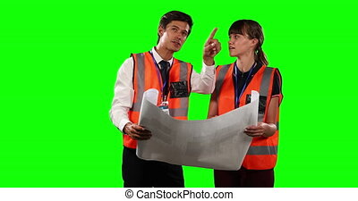 Front view of a site workers looking at a site map with green screen