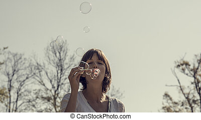 Front view of a woman blowing soap bubbles outside