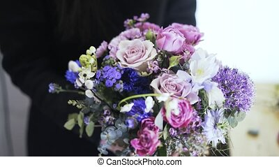 Front view of a woman florist holding a bouquet of beautiful flowers