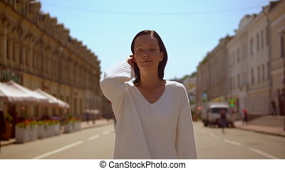 front view of a woman passing cafes and restaurants - lady...
