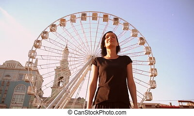 front view of a woman walking with a ferris wheel in the background