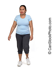 front view of a woman with sportswear walking on white background,