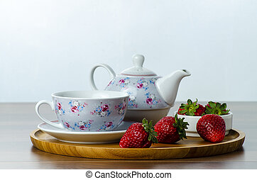 front view of a wooden tray on a table with three strawberries next to a cup of tea, seletive focus  white background