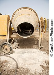 cement mixer - front view of a yellow working cement mixer