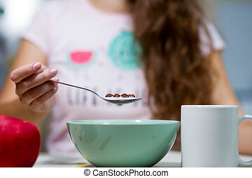 young woman with long hair holding a spoon with chocolate cereal over a plate