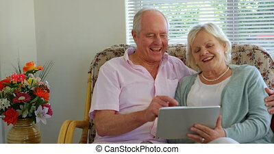 Front view of active Caucasian senior couple using digital tablet at nursing home 4k