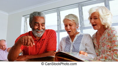 Front view of active Caucasian senior people looking at photo album in nursing home. They are interacting with each other 4k
