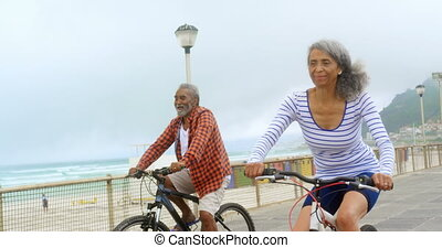 Front view of active senior African American couple riding a bicycle on promenade 4k