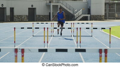 Front view of african american athlete doing hurdling - ...