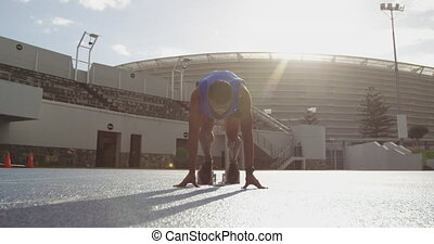 Front view of african american athlete running in stadium - ...