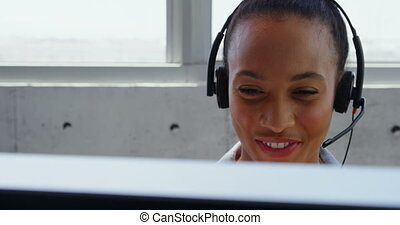 Front view of African American Businesswoman talking on headset at desk in a modern office 4k