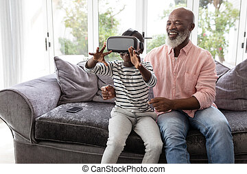 Grandson with grandfather using virtual reality headset in...