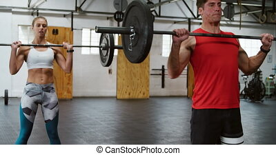 Front view of an athletic Caucasian man and woman wearing sports clothes cross training at a gym, standing and weight training with barbells, lifting them from the floor and raising them from chest level above their heads