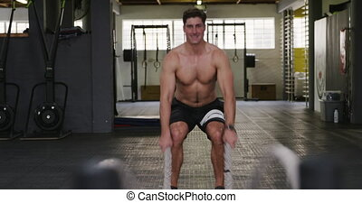 Front view of a shirtless, athletic Caucasian man wearing sports clothes cross training at a gym, working out with battle ropes