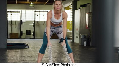 Front view of an athletic Caucasian woman wearing sports clothes cross training at a gym, working out with battle ropes