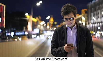 Front view of an attractive young businessman using his cell phone in night city