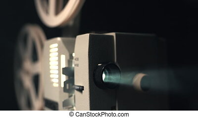 Front view of an old-fashioned antique Super 8mm film projector, projecting a beam of light in a dark room next to a stack of unraveled film reels