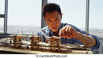 Front view of Asian male architect looking at architectural model in a modern office 4k