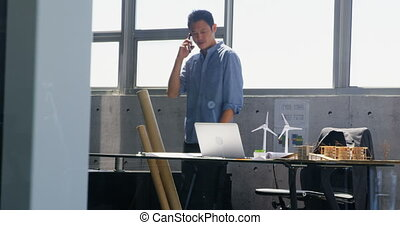 Front view of Asian male architect talking on mobile phone in a modern office 4k