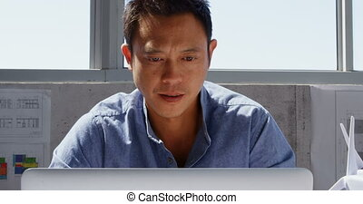 Front view of Asian male architect using laptop on desk in a modern office 4k