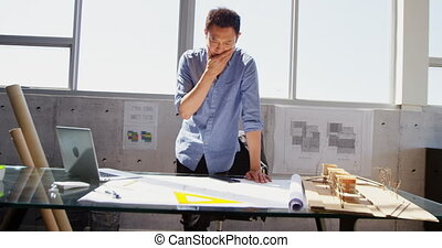 Front view of Asian male architect with hand on chin working at desk in office 4k