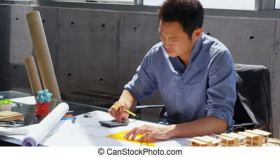 Front view of Asian male architect working on blueprint at desk in a modern office 4k