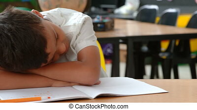 Front view of Asian schoolboy sleeping on desk in classroom at school 4k