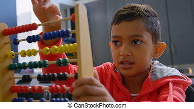 Front view of Asian schoolboy solving math problem with abacus at desk in a classroom at school 4k