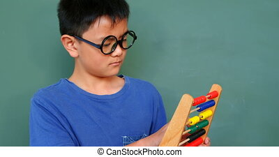 Front view of Asian schoolboy solving math problem with abacus in a classroom at school 4k