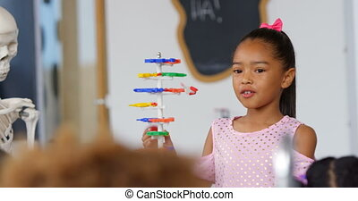 Front view of Asian schoolgirl explaining about dna ...