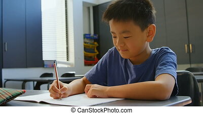 Front view of attentive Asian schoolboy studying at desk in classroom at school. He is writing on notebook 4k