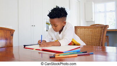 Front view of attentive black boy doing his homework at ...