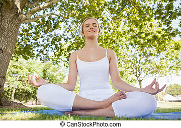 Front view of beautiful young woman sitting in a park meditating with closed eyes