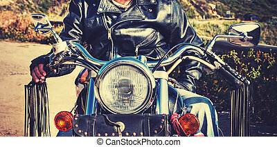 front view of  biker and motorcycle in vintage tone