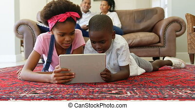Front view of black children lying on the floor and using digital tablet in a comfortable home 4k