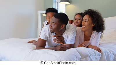 Front view of black family having fun in bedroom in a comfortable home 4k