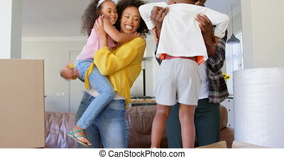 Front view of black family holding their children at comfortable home 4k