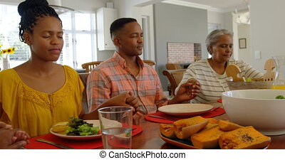 Front view of black family praying together at dining table in comfortable home 4k