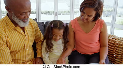 Front view of black family sitting on the couch and looking photo album in a comfortable home 4k