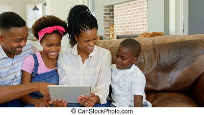 Front view of black family sitting on the couch and using digital tablet in a comfortable home 4k