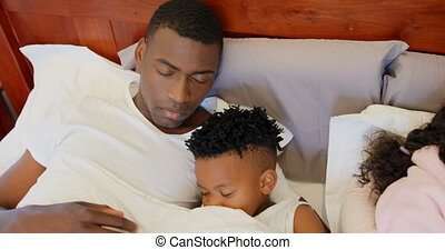 Front view of black family sleeping in bedroom at home 4k