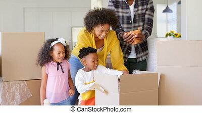 Front view of black family unpacking cardboard boxes at comfortable home 4k