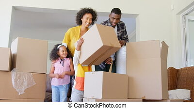 Front view of black family unpacking cardboard boxes at ...